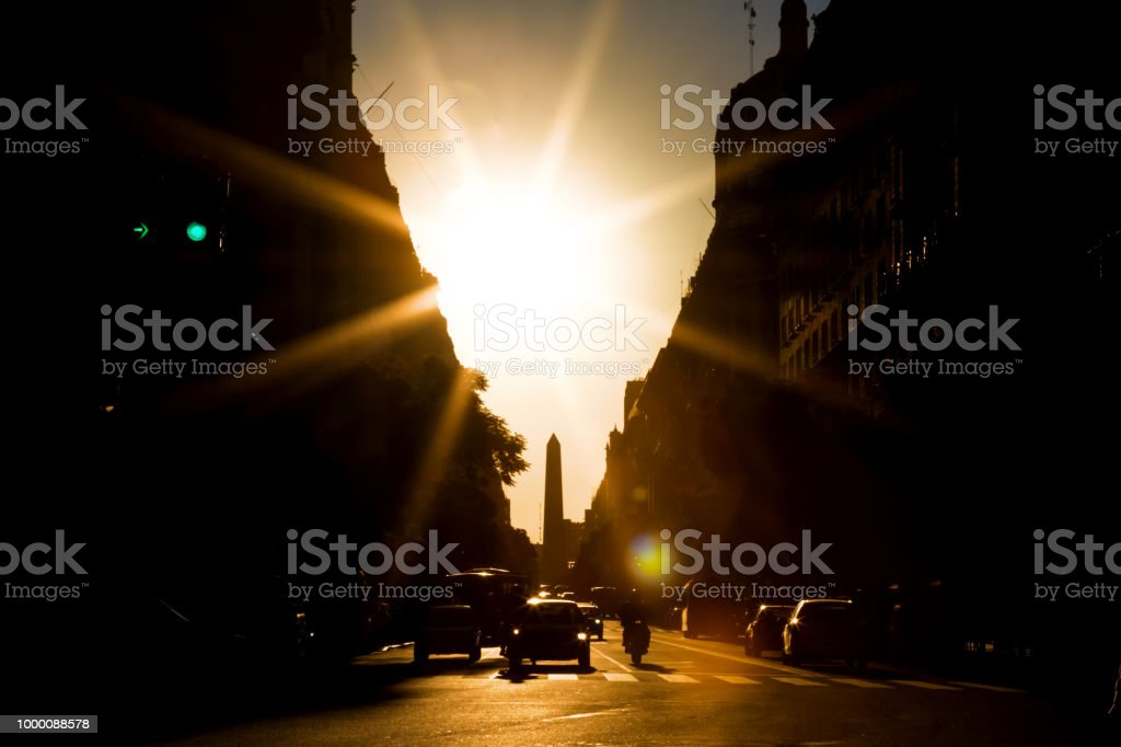 Avenue with solar backlight and obelisk of Buenos Aires in the background stock photo