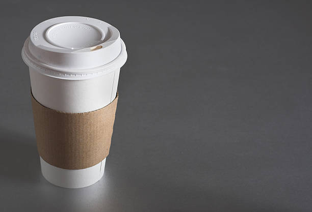 average coffee cup with blank sleeve to advertise coffee - paper coffee cup stock photos and pictures