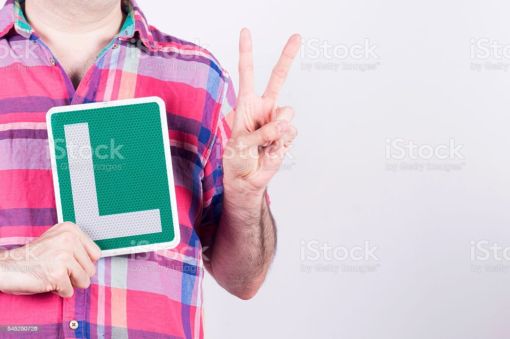 Average man holding his learner car driver plate. stock photo