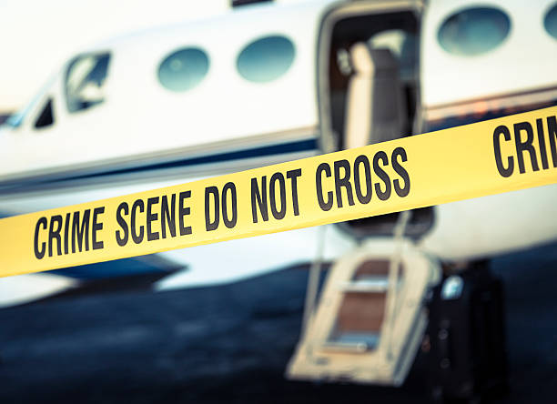 Aviation Crime Scene Crime scene cordon tape in front of a small airplane at an airport. smuggling stock pictures, royalty-free photos & images