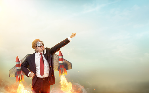 Businessman With Wings And Rockets Flying In The Sky
