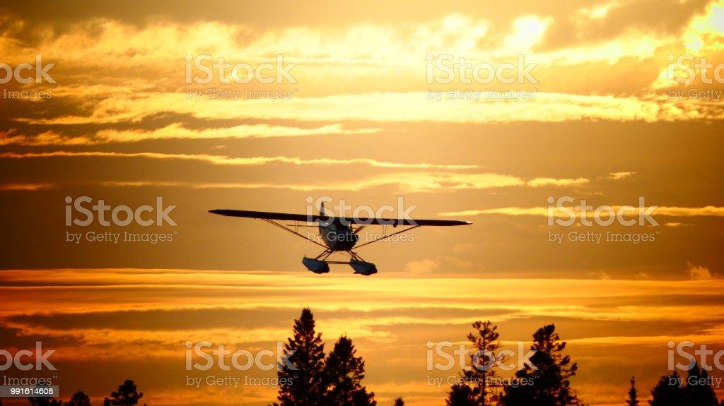 Avion dans un coucher de soleil au dessus de la montagne stock photo