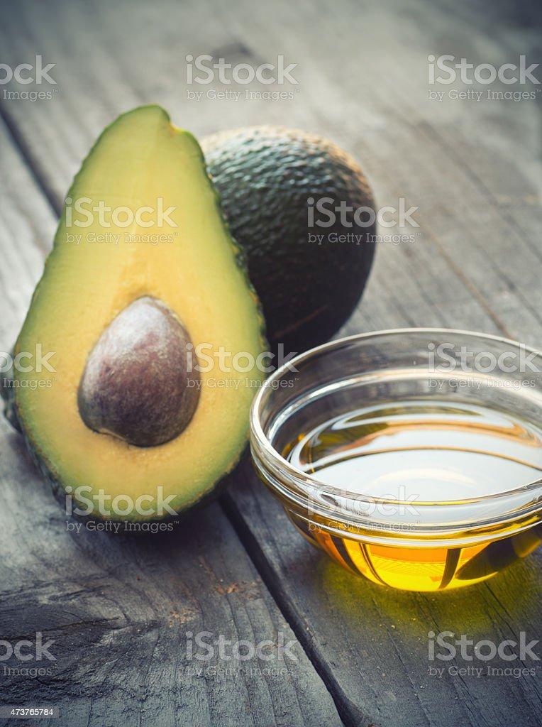 Avocado and avocado oil on wooden surface stock photo