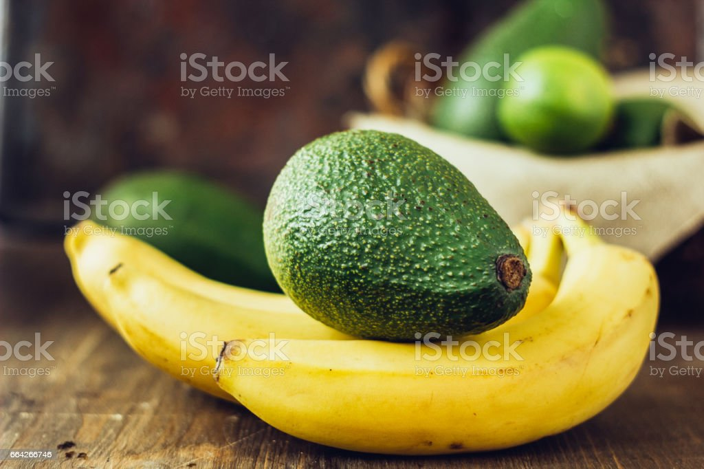 Avocado and banana over brown wooden background. stock photo