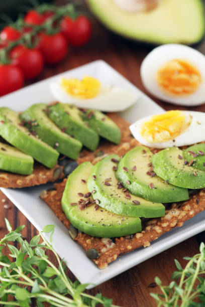 Avocado and boiled egg on pumpkin seeded crackers - shallow dof stock photo