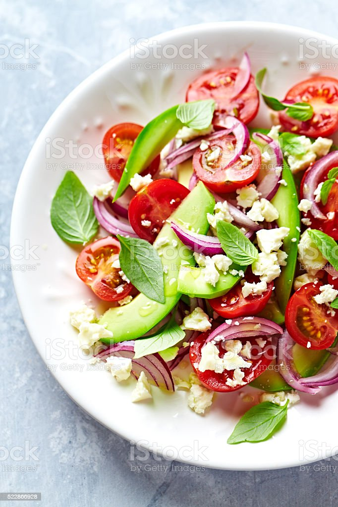 Avocado and Cherry Tomato Salad with Feta and Basil stock photo