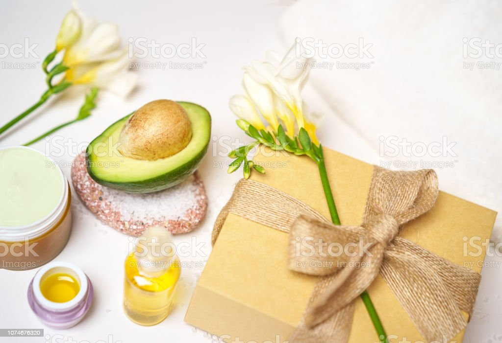 avocado and jar of cream oil gift box flowers sea salt and towel on a white background. Avocado skin care facial mask. Facial treatment preparation concept for gift. stock photo