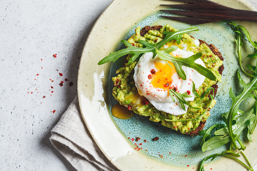 Avocado and poached egg toast on rye bread. Healthy breakfast concept.
