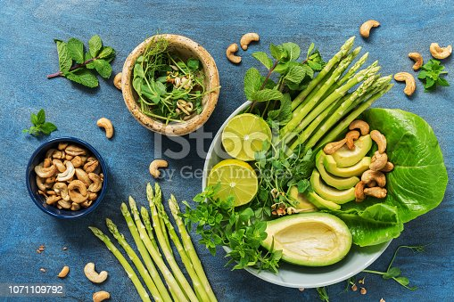 istock Avocado, asparagus, micro greens, lime, mint,basil, lettuce and cashew nuts. Detox bowl buddha. Blue rustic background, top view. Clean, wholesome food. 1071109792