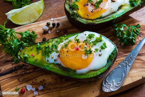 istock Avocado baked with eggs. Wooden background, fresh parsley, ground pepper. 663904956