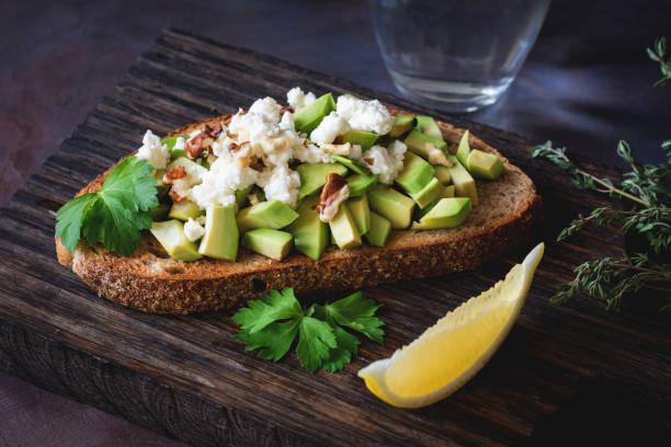 avocado, cheese and walnuts on toasted bread - spieltag vorspeisen stock-fotos und bilder