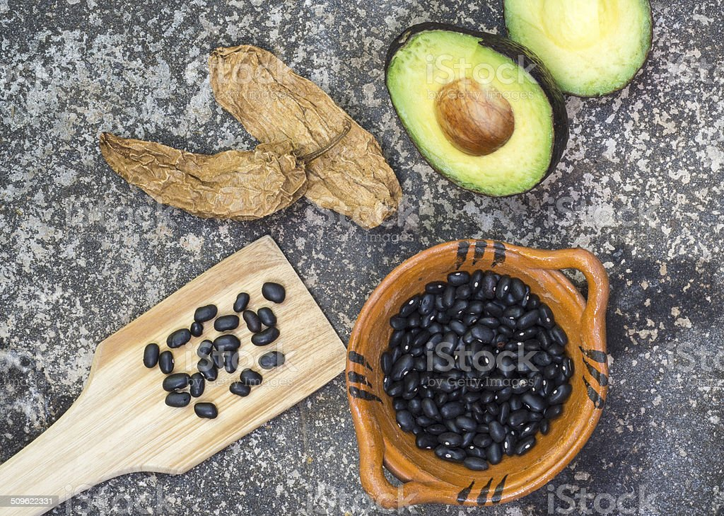 Avocado, chile peppers and black beans on stone grinder stock photo