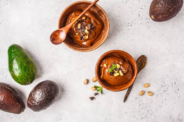 Avocado chocolate mousse with pistachios in wooden bowl on white background. stock photo