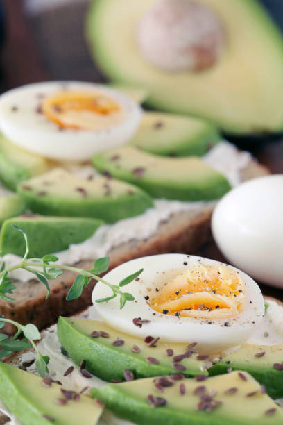 Avocado, cream cheese and boiled eggs on wholemeal bread - shallow dof stock photo