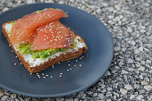 A toasted bread with avocado, cream cheese and salmon, sprinkled with sesame seeds on a plain plate and marble background with copy space