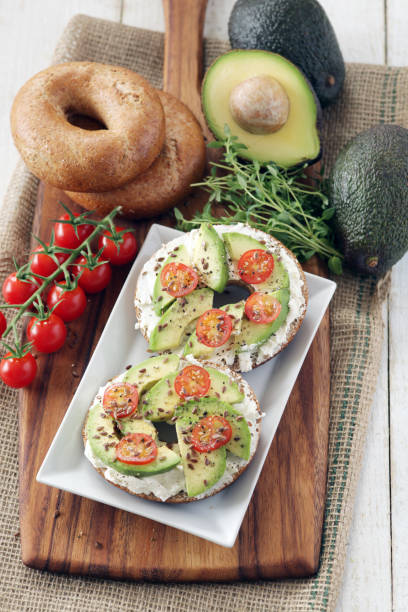 Avocado, cream cheese and tomato on wholemeal bagels stock photo