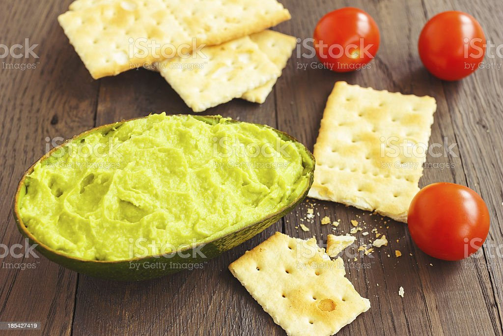 Avocado cream,biscuits and small tomatoes royalty-free stock photo