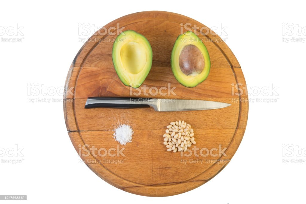 Avocado Cut In Half With Knife Salt And Cedar Nuts On The Wooden