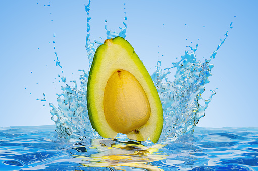istock Avocado cut in half with water splashes, 3D rendering on blue background 1205385728