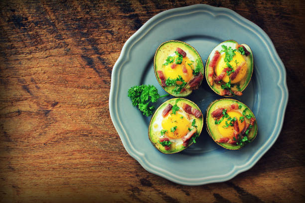 Avocado Egg Boats with bacon on dark wooden background. Top view stock photo