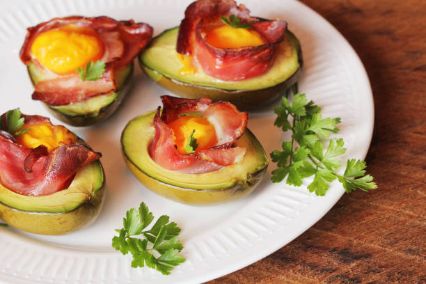Avocado Egg Boats with bacon on white plate. Wooden background. Top view stock photo