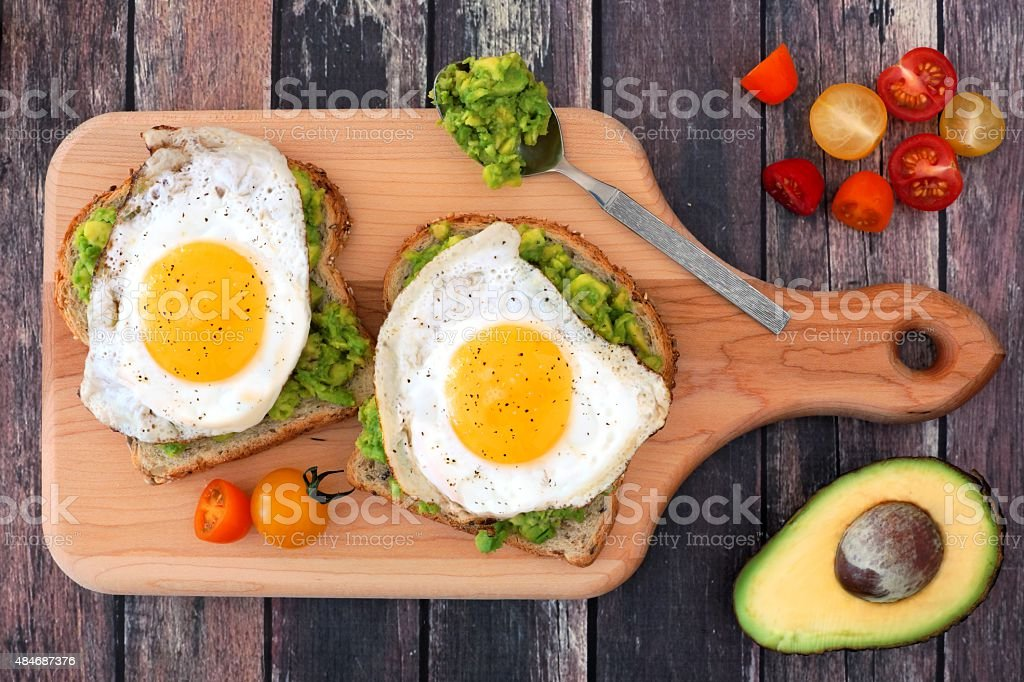 Avocado, egg open sandwiches on paddle board stock photo