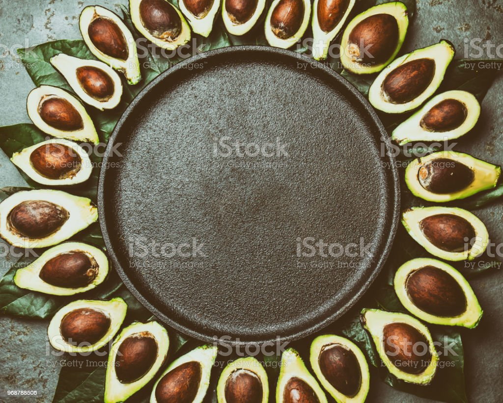 Avocado. Frame made from avocado palta and avocado tree leaves around black plate. Guacamole ingredients. Healthy fat, omega 3. Half of avocado. Top view. Copy space. stock photo