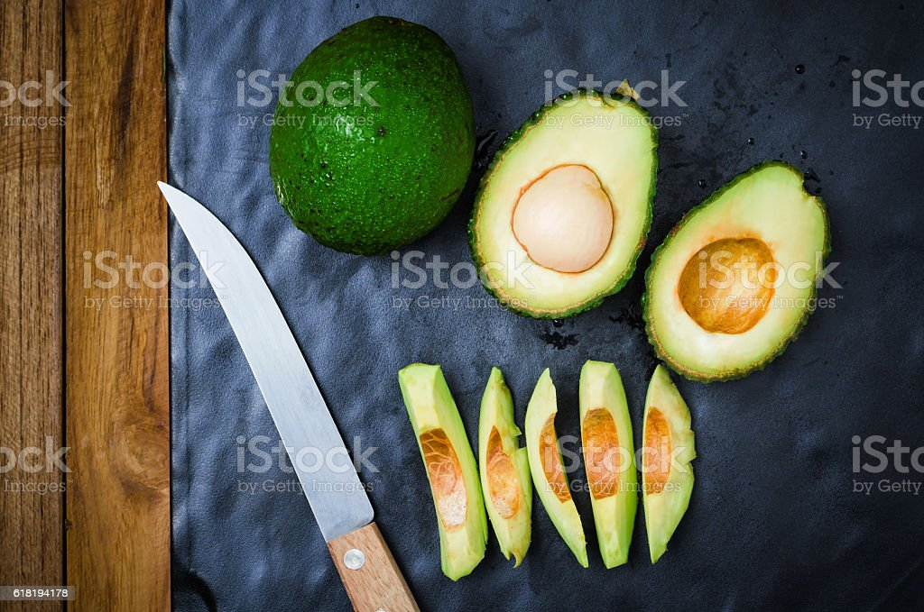 Avocado fruit and sliced avocad on black stock photo
