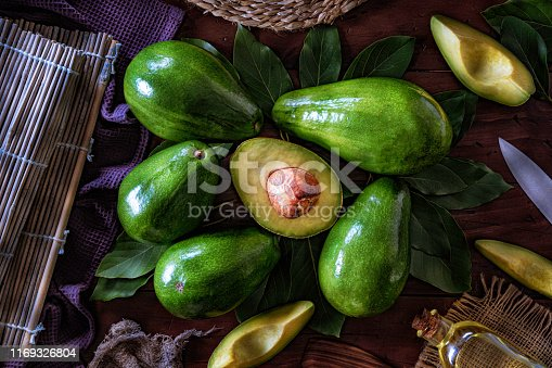 Avocado fruits and sliced avocados on a wooden table in a rustic kitchen