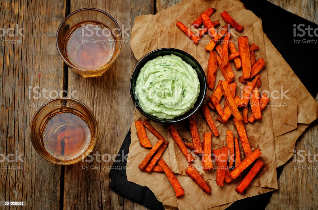 Avocado greek yogurt lime cilantro dip with baked Sweet Potato Fries stock photo