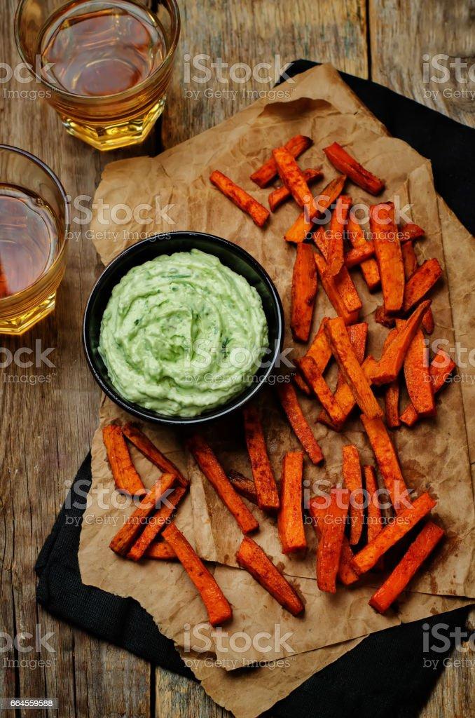 Avocado greek yogurt lime cilantro dip with baked Sweet Potato Fries royalty-free stock photo