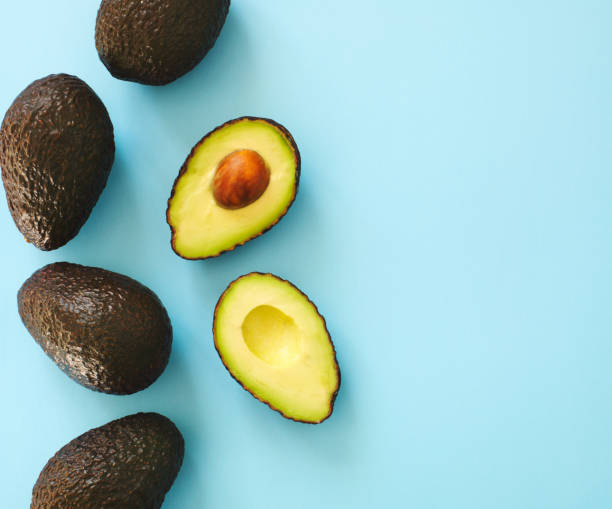 Avocado halves and whole on a blue speckle, top viev. stock photo