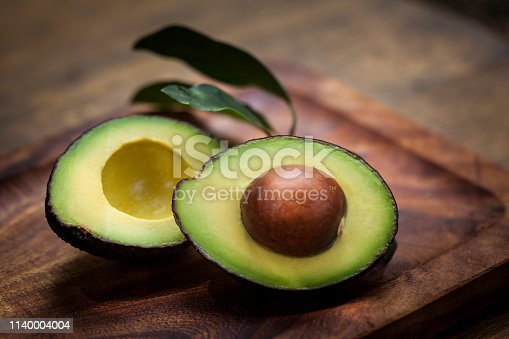 Avocado Halves on a wooden board with avocado leaves