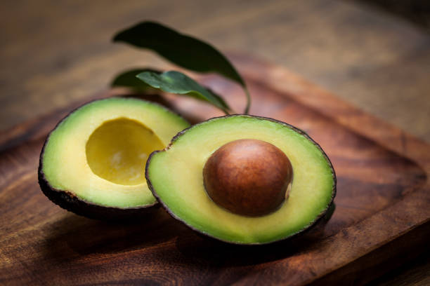 Avocado halves on a wooden board stock photo