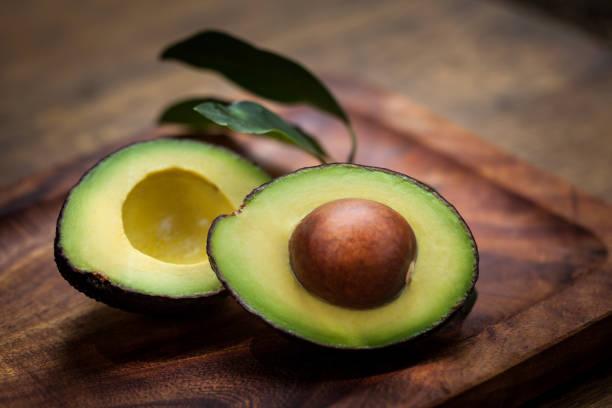 avocado halves on a wooden board - avocado stock photos and pictures
