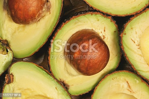 Avocado halves, with brown seed inside, closeup detail view from above