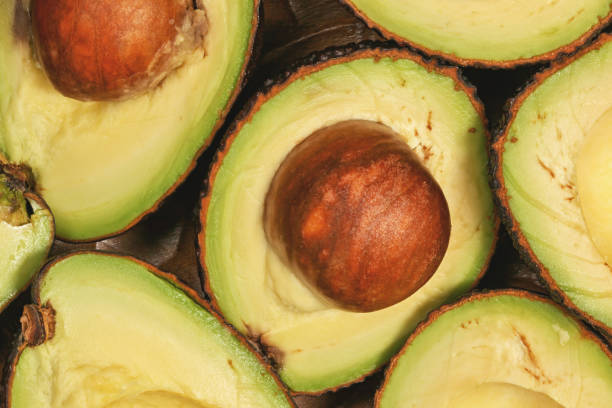 Avocado halves, with brown seed inside, closeup detail view from above stock photo