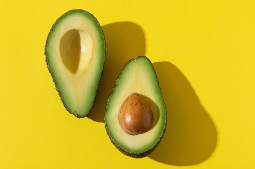 Avocado halves close up with trendy hard shadow and hard light on yellow background, minimalist