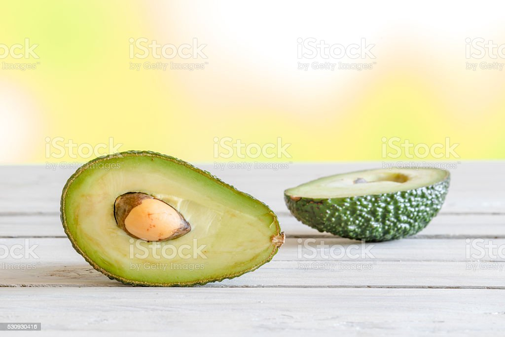Avocado in half on a table stock photo