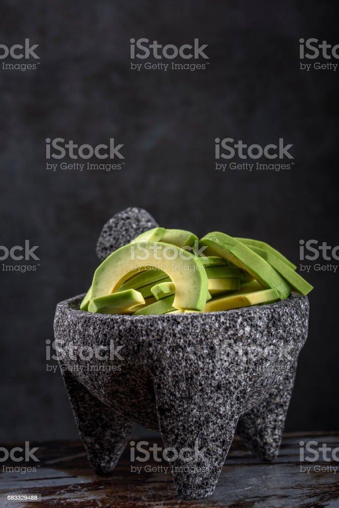 Avocado in stenen mortier en een stamper royalty free stockfoto