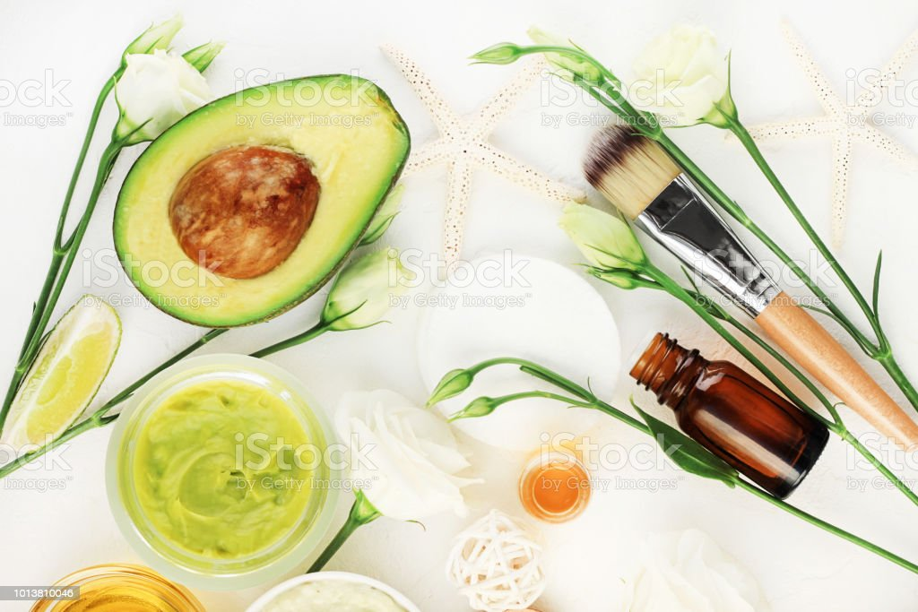 Avocado mask for beautiful skin and hair treatment. Facial mask in jar with essential oils and white blossom, stock photo
