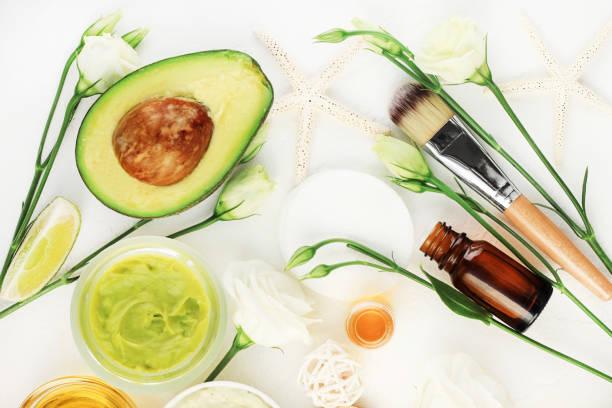 avocado-maske für schöne haut und haare behandlung. gesichtsmaske in glas mit ätherischen ölen und weißen blüten, - makeup selbst gemacht stock-fotos und bilder