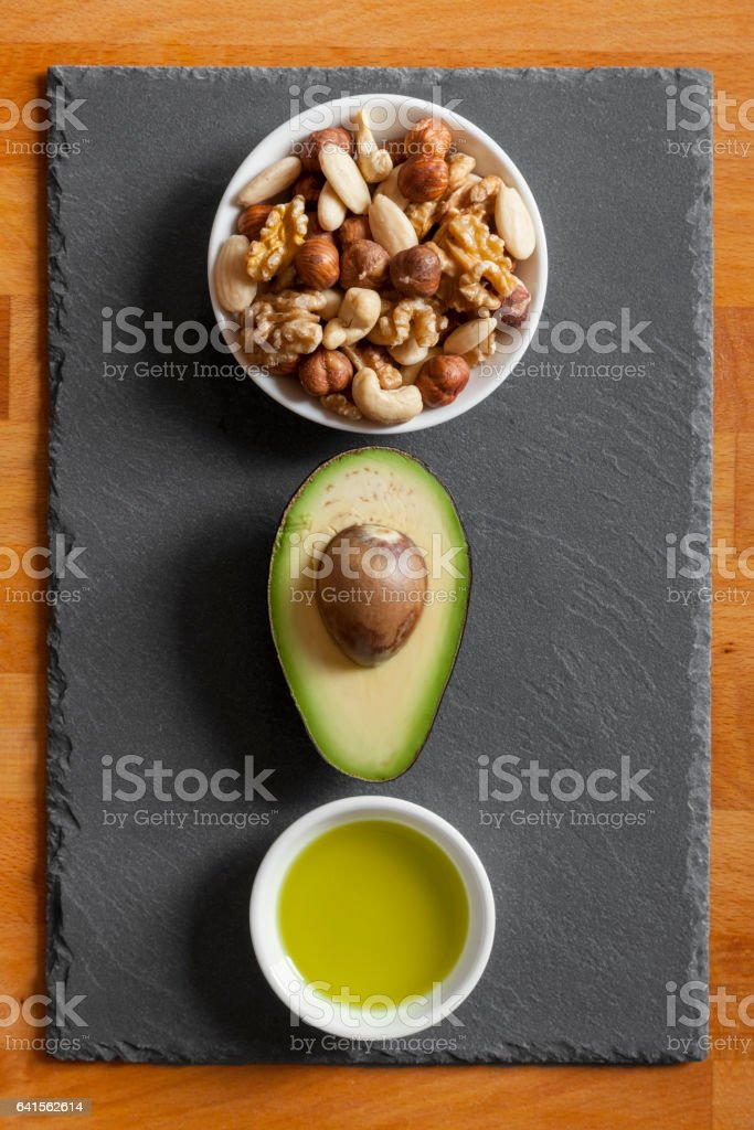 Avocado, Mixed nuts and Olive Oil on Table Top stock photo