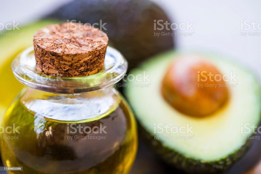 Avocado oil bottle with avocados fruits, healthy fats oil closeup