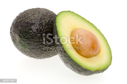 A whole avocado and another cut in half - shot in the studio with a white background
