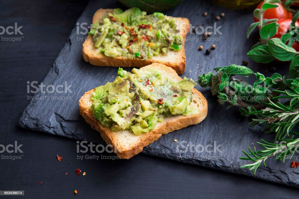 Avocado on toast with chili flakes , herbs and cherry tomatoes stock photo
