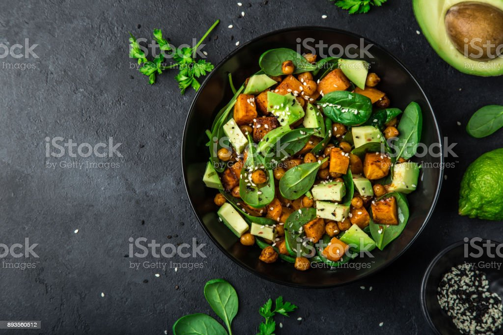Avocado, quinoa, roasted sweet potato, spinach and chickpeas salad in black bowl. stock photo