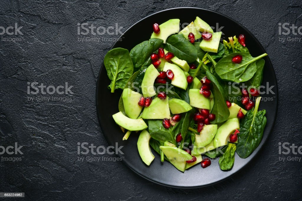 Avocado salad with baby spinach and pomegranate stock photo