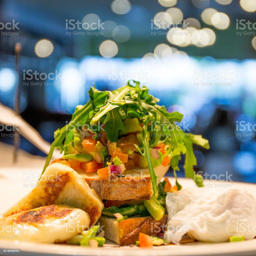 Avocado Salsa, Poached Eggs Grilled Halloumi stock photo