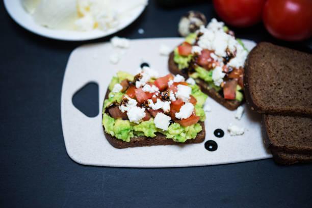 Avocado Sandwich mit Käse und Tomaten. Roggen Toast mit weißen Weichkäse, Avocado und Tomaten gegossen Balsamico-Sauce für gesundes Frühstück oder Snack – Foto